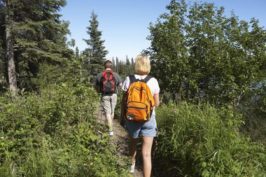 Couple Walking Along Trail In Forest
