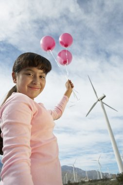 Girl Holding Balloons At Wind Farm