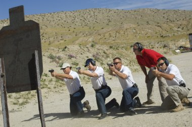 Four Firing Guns At Shooting Range