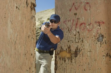 Officer Aiming Hand Gun At Firing Range