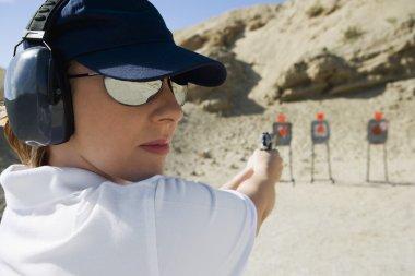 Woman Aiming Hand Gun At Firing Range