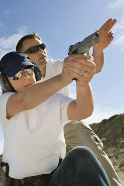 Instructor Assisting Woman With Hand Gun At Firing Range