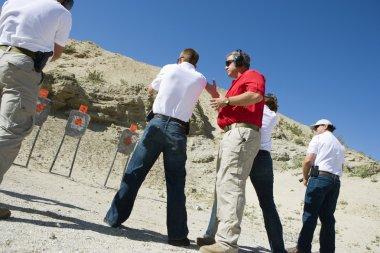 Instructor Assisting Aiming Guns At Firing Range