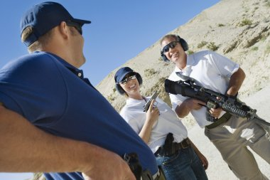 Instructor with man and woman at firing range