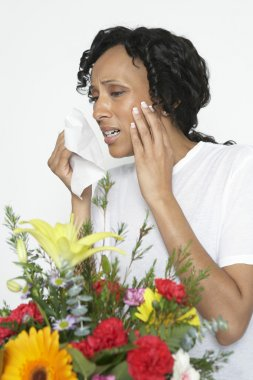 Woman With Allergy Holding Tissue Near Flowers