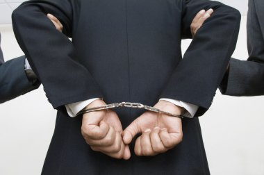 Businessman With Handcuffs While Partners Holding His Arms