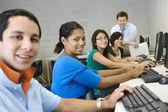 Studenty středních škol s profesorem v počítačové učebně