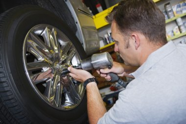 Mechanic Fixing Bolts With Electronic Screw Fitter