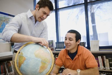 Professor Pointing Out Location On Globe To Student