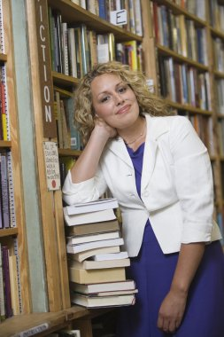 Female Librarian Standing By Stack Of Books