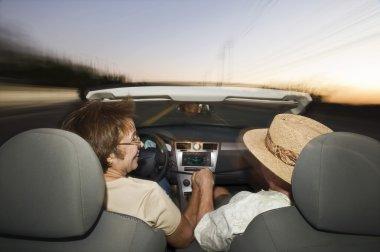 Senior Couple Driving Convertible