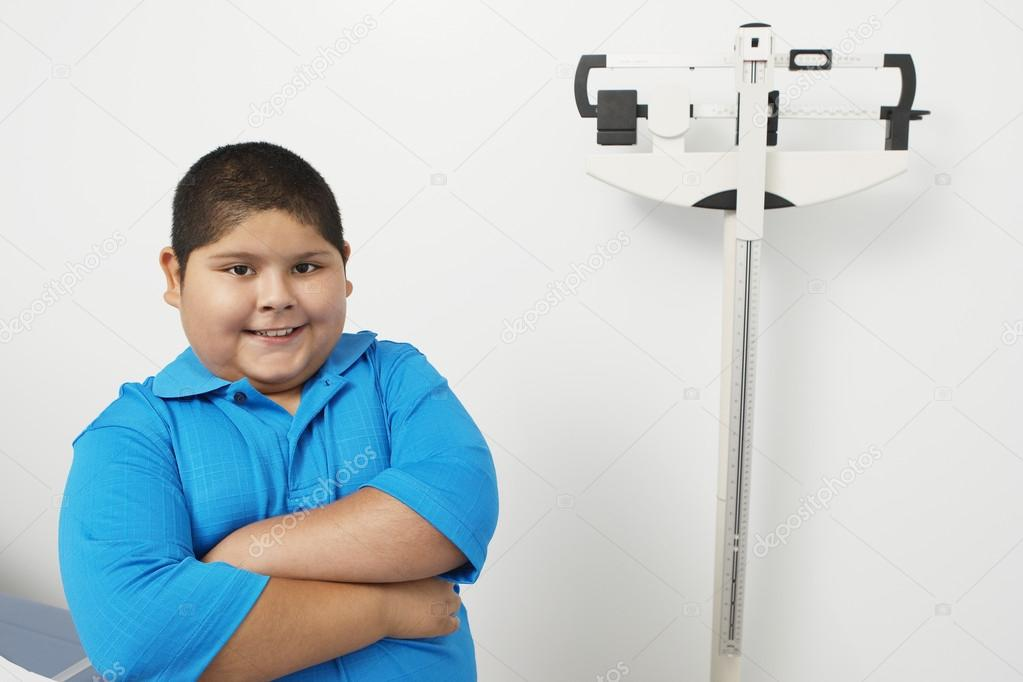 Boy Standing By Weighing Scale In Clinic