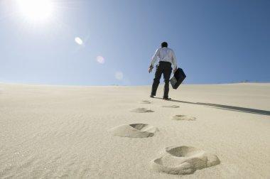 Businessman Walking With Briefcase In Desert