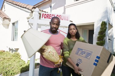 Portrait Of Sad Bankrupt Couple Moving Out Of House