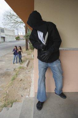 Thief Hiding Behind Wall Looking At Girls
