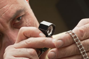 Close up of man looking at jewelry through magnifying glass