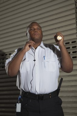 Security Guard Holding A Torch Light