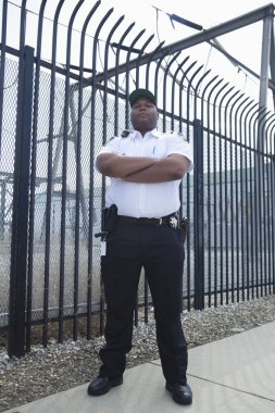 Security Guard Standing In Front Of The Prison Fence