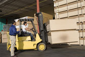 Photo Warehouseman and forklift truck driver