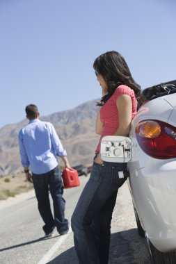 Woman on call by car while man with gasoline can