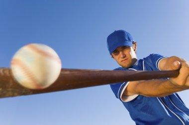 Baseball player hitting ball with bat