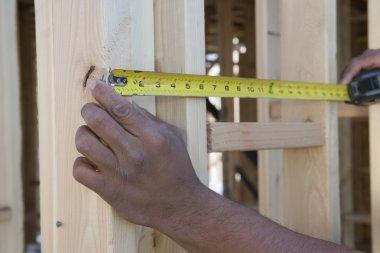 Hands measuring between boards