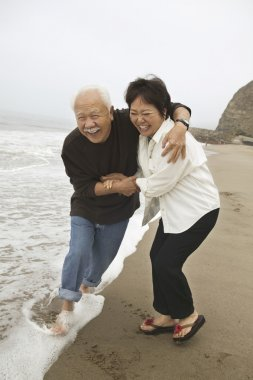 Mature couple playing in surf