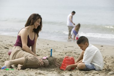 Mother building sandcastles with son