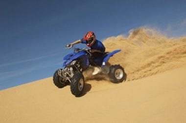Low angle view of a man riding quad bike in desert against the blue sky stock vector