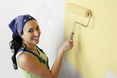 Woman applying paint on a wall