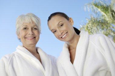 Women in bathrobes against blue sky at spa
