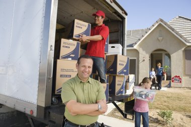 Family and worker unloading boxes
