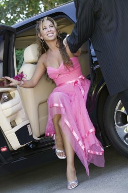 Girl in dress being helped out of limo
