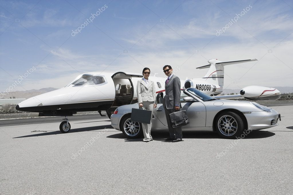 Business couple in front of convertible and private jet