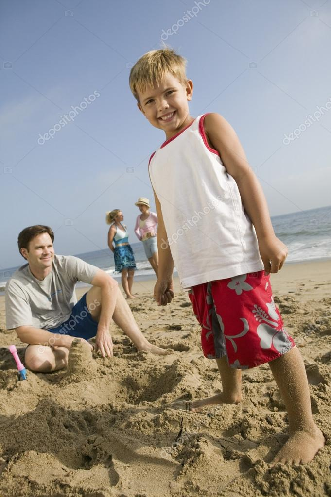 Boy Playing in Sand with Family