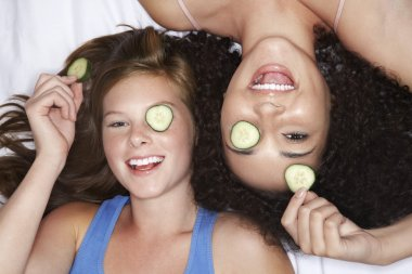 Teenage Girls lying with cucumbers in eyes