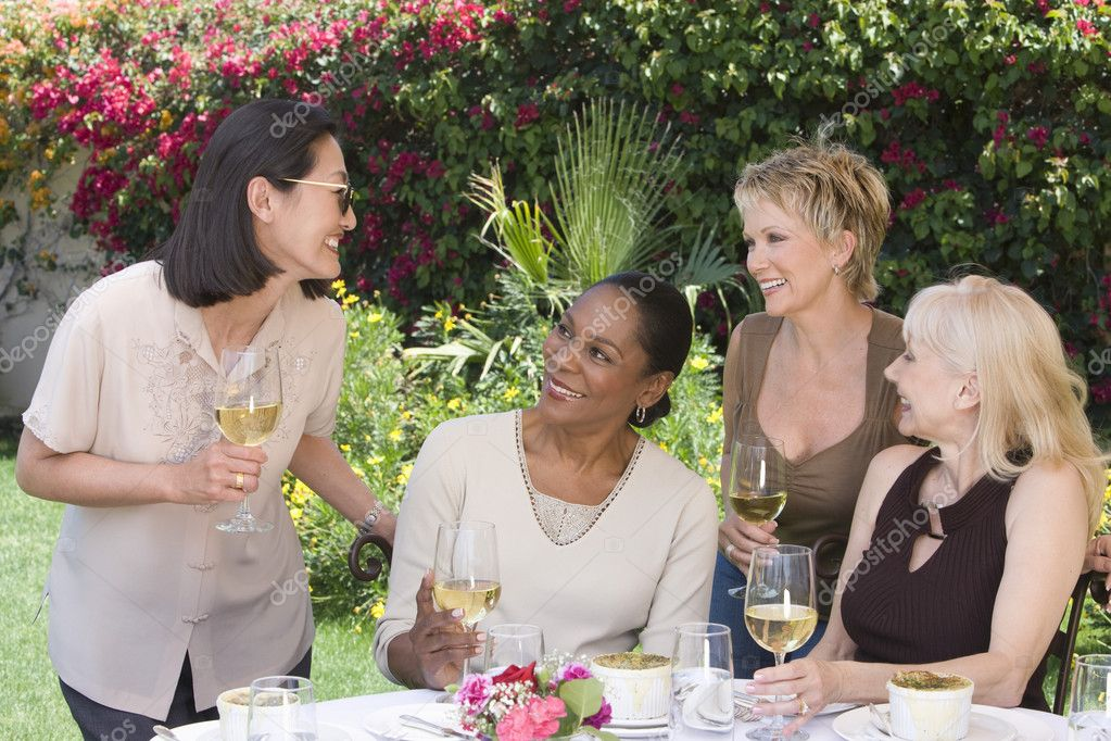 Women chatting with wine glasses