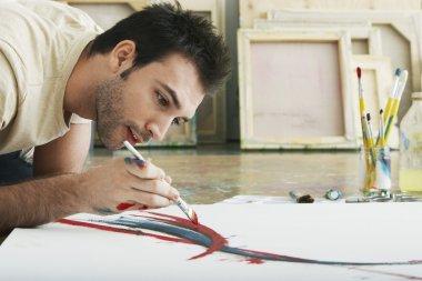Man painting on canvas on studio floor stock vector