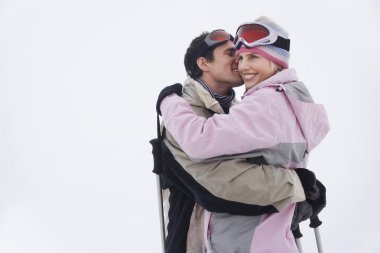 Side view of a happy couple in warm clothing embracing in snow