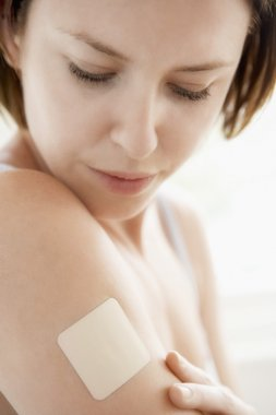 Woman looking at nicotine patch