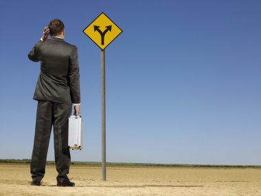 Confused businessman looking at desert road sign