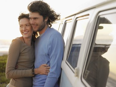 Young couple embracing near van