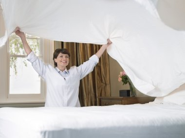 Smiling woman making bed