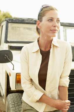 Woman standing in front of car