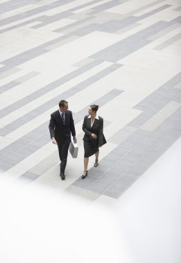 Businessman and businesswoman walking across