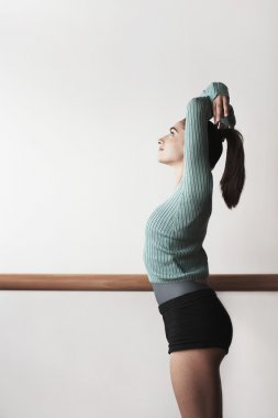 Ballet Dancer with arms overhead at bar