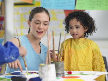 Art teacher with little girl painting