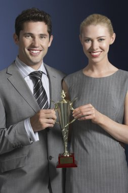 Business people holding trophy