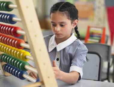 Schoolgirl  counting the on abacus