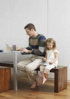 Father with laptop and daughter drawing